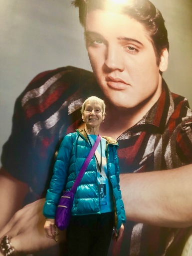 A photo of my lovely old mum standing in front of large photo of young Elvis.
