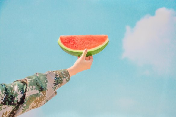 Photo of hand holding slice of yummy watermelon with blue sky behind it. Summer!