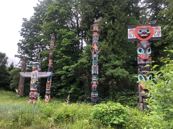 Pic of five large painted totem poles in front of small patch of forest. Varying heights and designs.