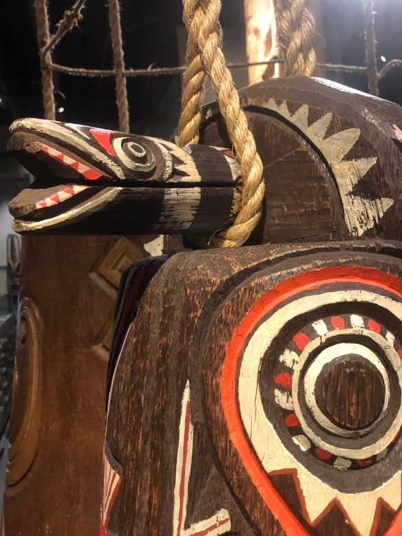Close-up pic of a wooden piece of art  showing First Nation's symbols and colors (from University of British Columbia-Museum of Anthropology).