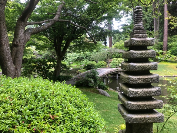 Photo of serene Japanese garden, the Nitobe Japanese Garden, with stone wedding lamps, a small bridge and lots of trees and plants.