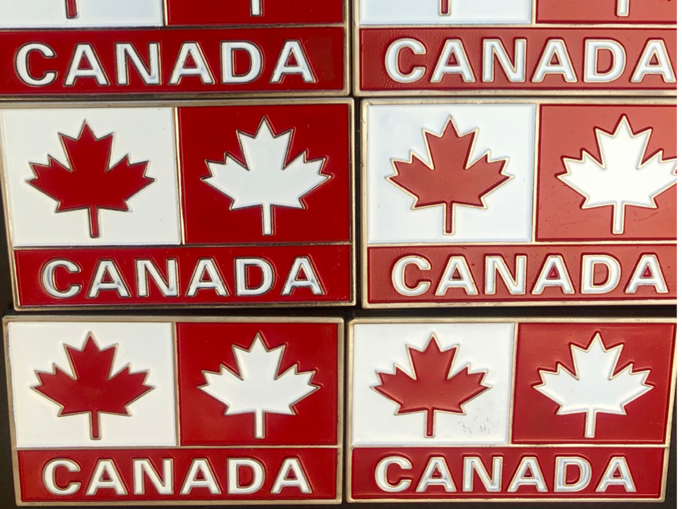 Canadian flag fridge magnets on display in shop.