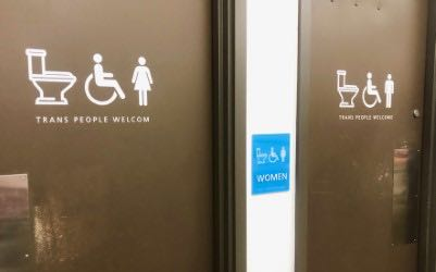 Pic of trans-welcoming bathroom signs.